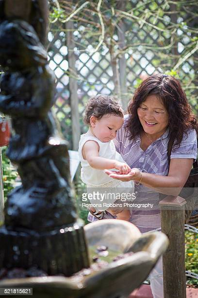 Grandmother and granddaughter feeding at fishpond in zoo