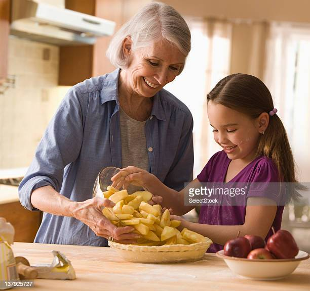 Grandmother and granddaughter filling in pie