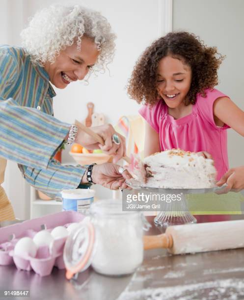 Grandmother and granddaughter frosting cake