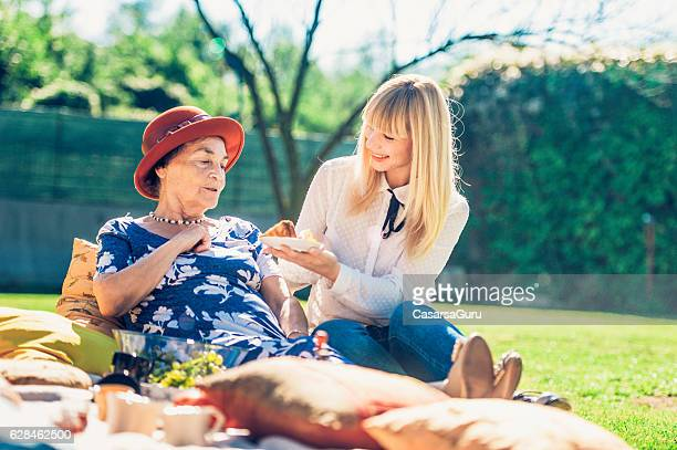 Grandmother and Granddaughter Having a Picnic Outside