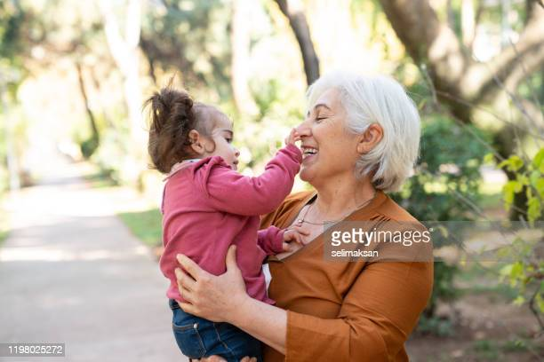 grandmother and granddaughter having good time in public park - images foto e immagini stock
