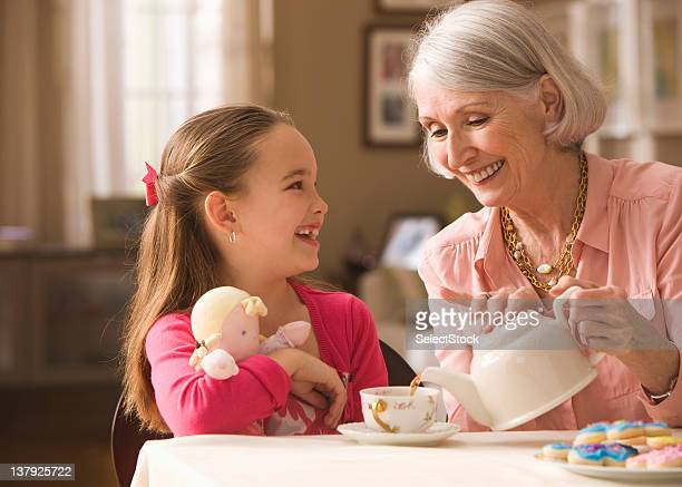 grandmother and granddaughter having tea party - tea party stock pictures, royalty-free photos & images