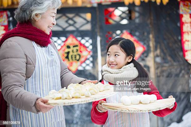 Grandmother and granddaughter holding Chinese Dumplings