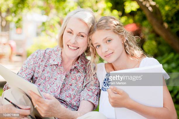 grandmother and granddaughter holding sketch pads outdoors - generation gap stock pictures, royalty-free photos & images