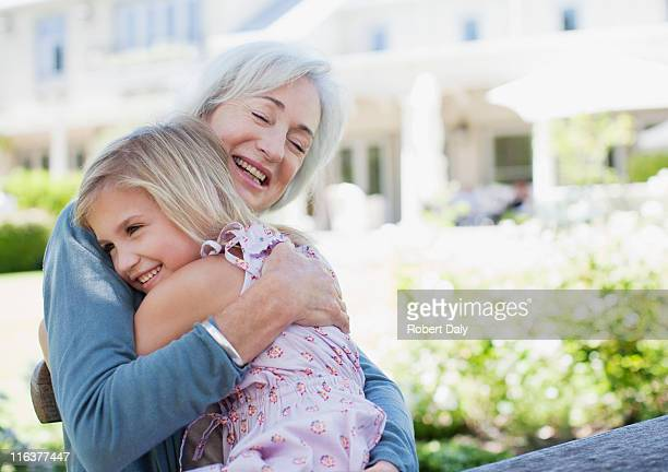 Grandmother and granddaughter hugging in backyard