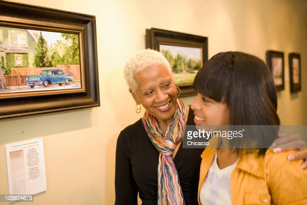 grandmother and granddaughter hugging in gallery - la art show stock pictures, royalty-free photos & images