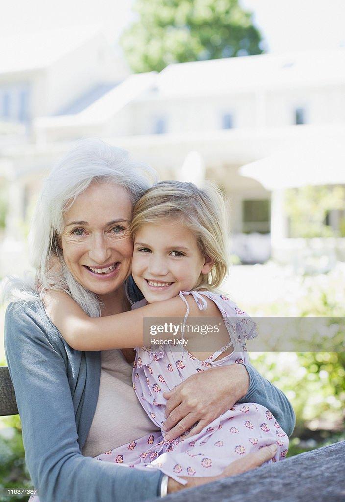 Grandmother and granddaughter hugging in garden : Stock Photo