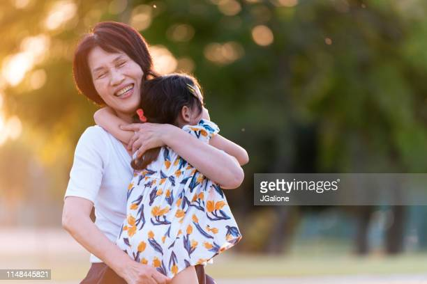 grandmother and granddaughter hugging outdoors in the park - jgalione stock pictures, royalty-free photos & images