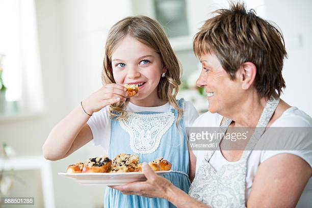 Grandmother and granddaughter in kitchen with plate of pastry