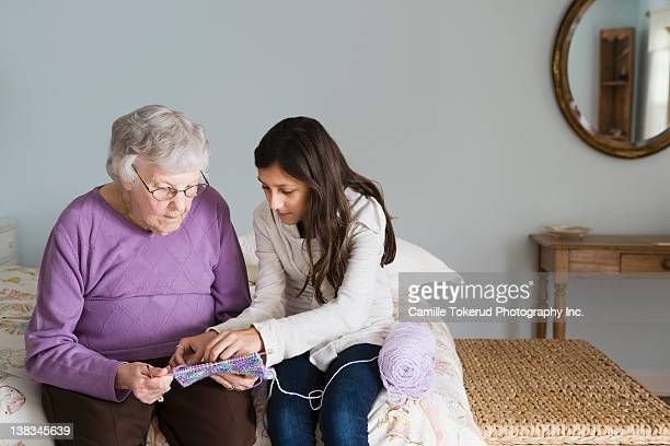 grandmother and granddaughter knitting together - teenager alter stock-fotos und bilder