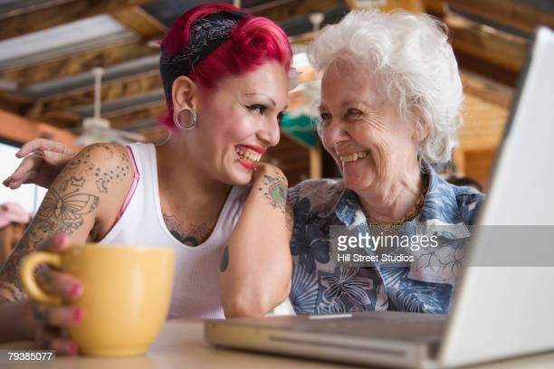 Grandmother and granddaughter looking at laptop