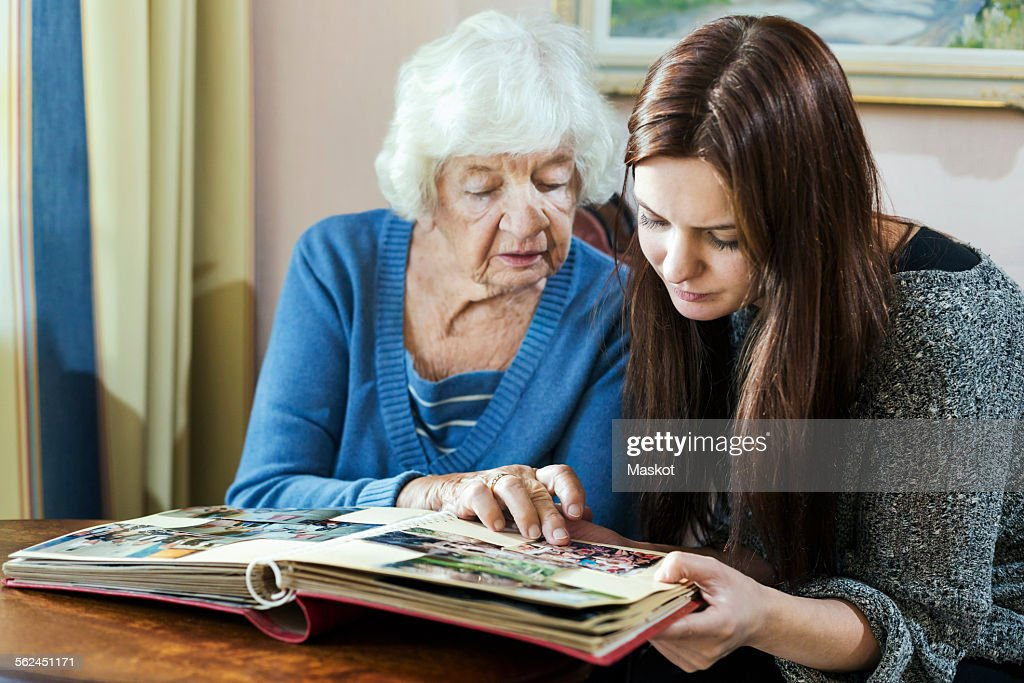 Grandmother and granddaughter looking at photo album in house : Stock Photo