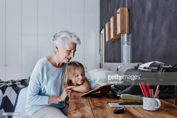 Grandmother and granddaughter looking at tablet at home