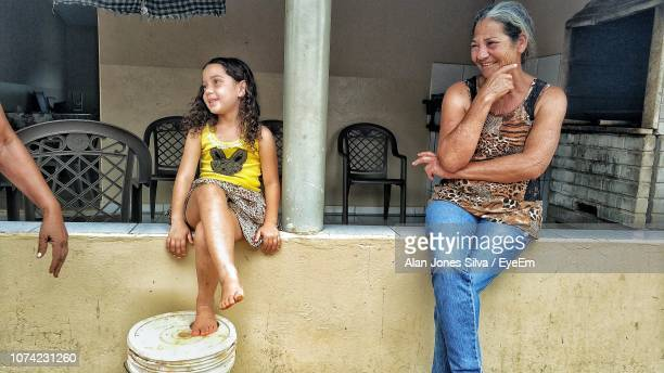 Grandmother And Granddaughter Looking Away While Sitting On Retaining Wall