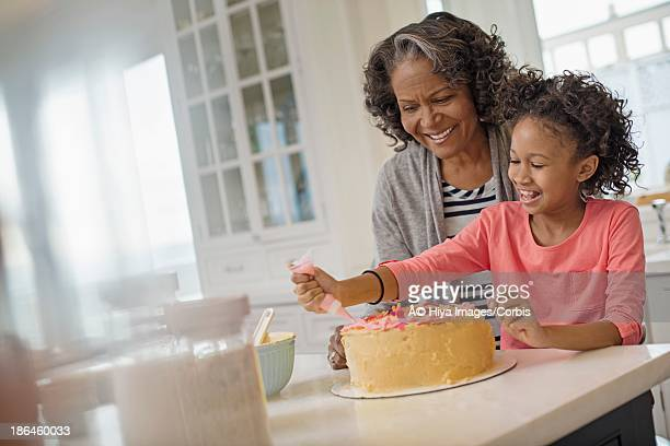 Grandmother and granddaughter (6-7) making cake in kitchen