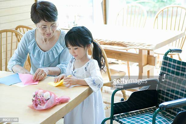 Grandmother and granddaughter making origami