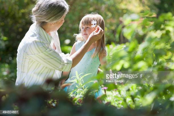 Grandmother and granddaughter picking flowers