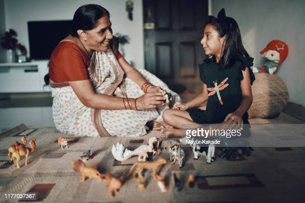 grandmother and granddaughter playing animal toys together - traditional clothing stock pictures, royalty-free photos & images