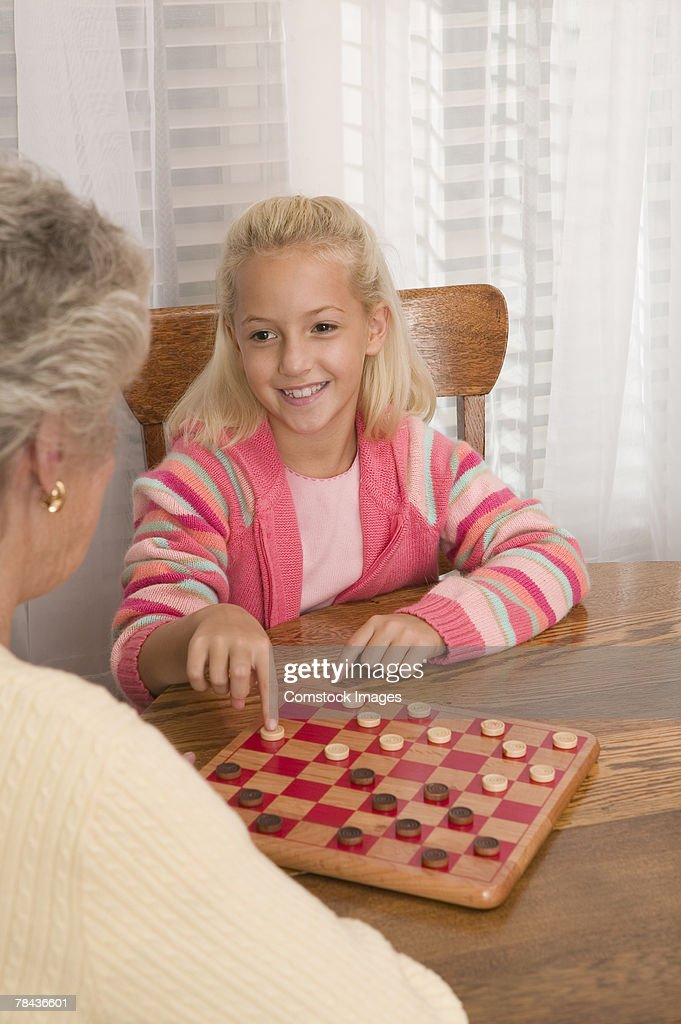 Grandmother and granddaughter playing checkers : Stockfoto