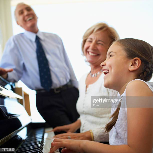 grandmother and granddaughter playing piano while grandfather listening - キーボード奏者 ストックフォトと画像