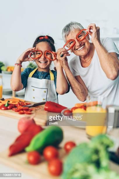 grand-mère et sa petite-fille jouer avec légumes - mamie humour photos et images de collection