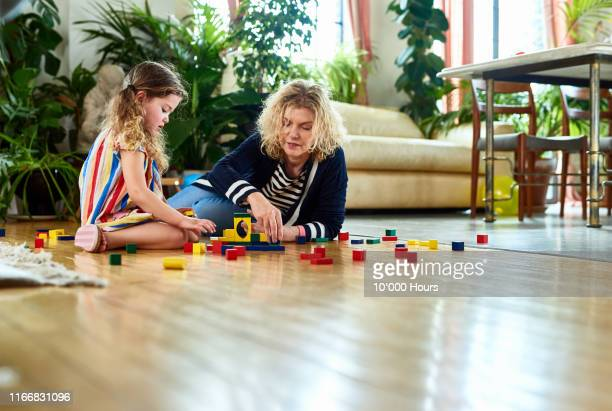 grandmother and granddaughter playing with wooden blocks at home - parent stock pictures, royalty-free photos & images