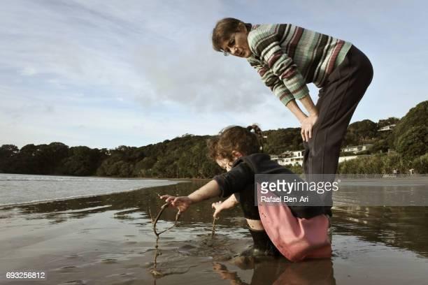 grandmother and granddaughter plays on the beach - rafael ben ari stock-fotos und bilder