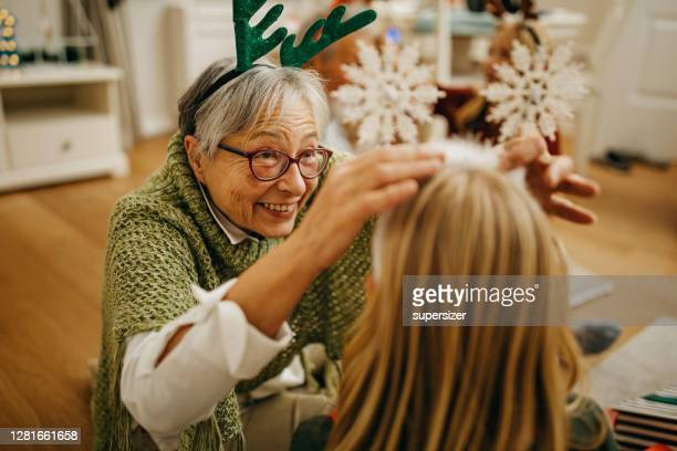 grandmother and granddaughter preparing for new year - 70 year old man stock pictures, royalty-free photos & images