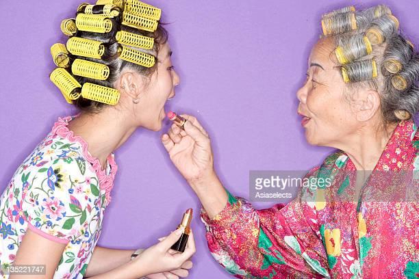 grandmother and granddaughter putting on lipstick. - beautiful granny stock-fotos und bilder