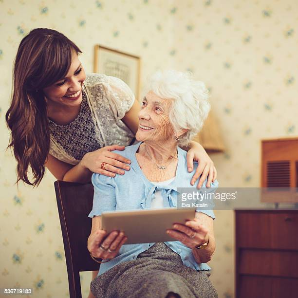 Grandmother and granddaughter reading a tablet at home