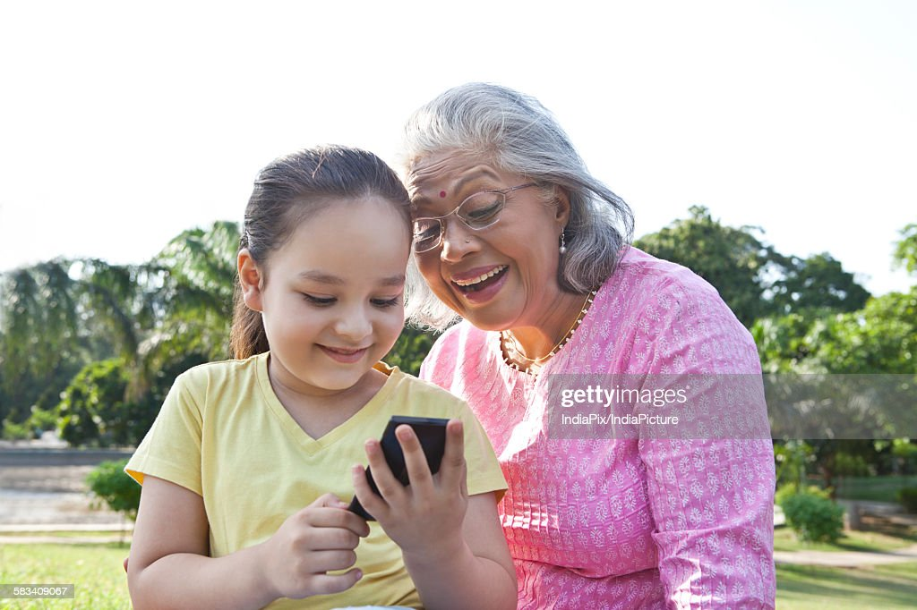 Grandmother and granddaughter reading an sms : Stock Photo