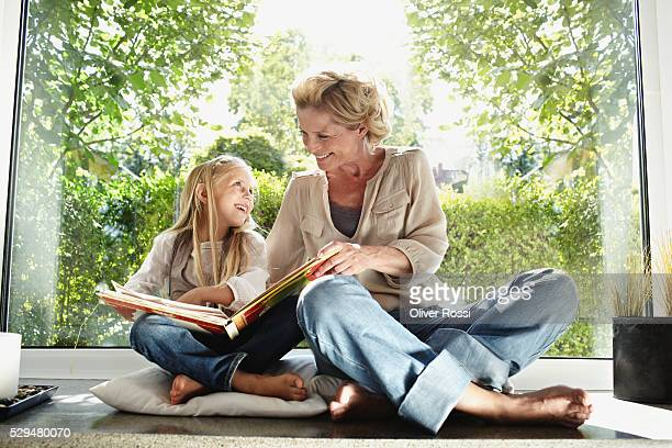 grandmother and granddaughter reading together - 50 59 years stock pictures, royalty-free photos & images