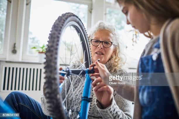 Grandmother and granddaughter repairing bicycle at home