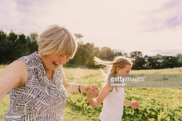 grandmother and granddaughter roller skating - british granny stock photos and pictures