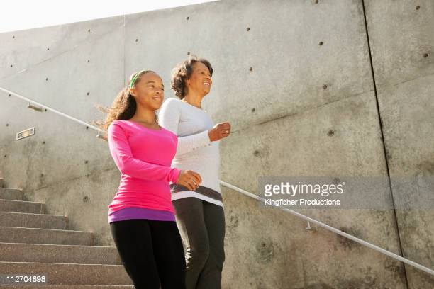 Grandmother and granddaughter running down urban steps
