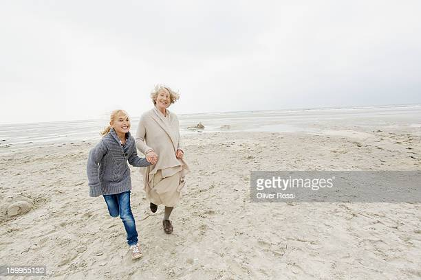 Grandmother and granddaughter running on the beach