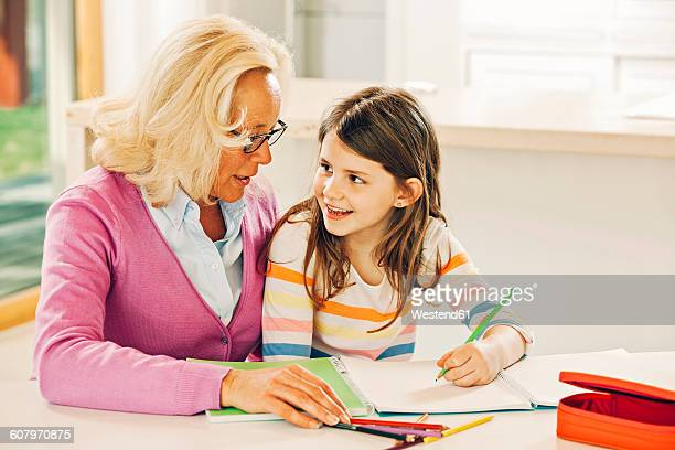 grandmother and granddaughter sitting at table with coloring book - colouring book stock photos and pictures