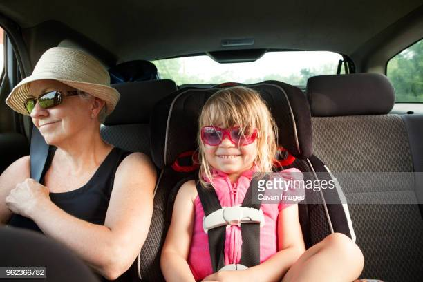 Grandmother and granddaughter sitting in car