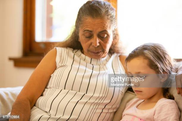 Grandmother and granddaughter sitting on a lounge