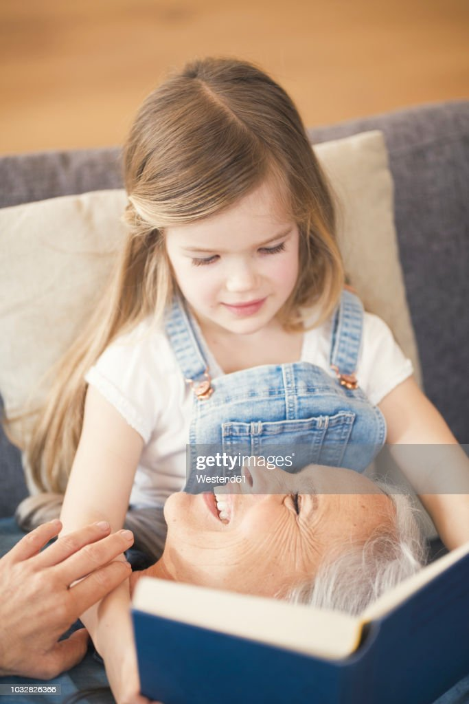 grandmother and granddaughter sitting on couch reading together a