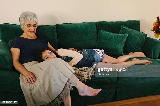 grandmother and granddaughter sitting on sofa in living room - girls with short skirts - fotografias e filmes do acervo