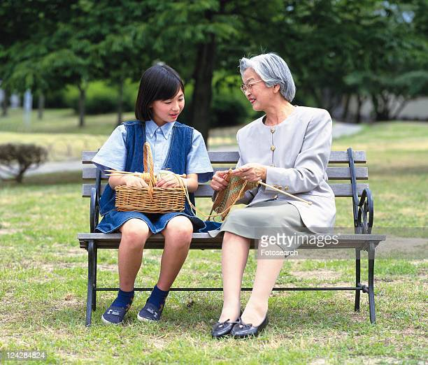 Grandmother and granddaughter sitting together on a bench, Front View