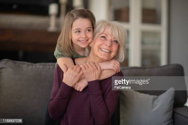 a grandmother and granddaughter snuggle together on the couch. - fat granny stock pictures, royalty-free photos & images