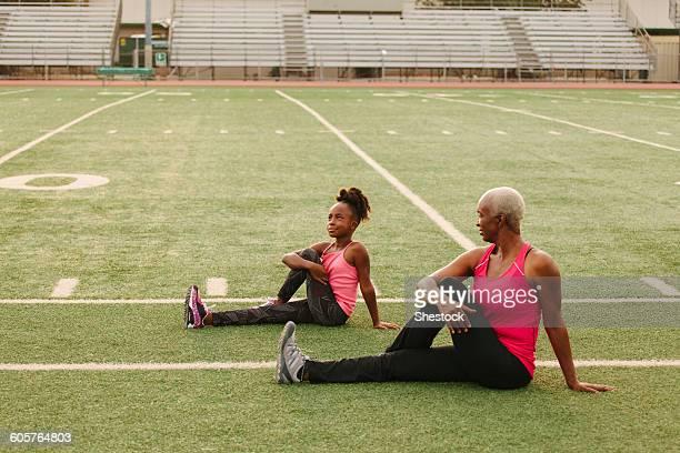 grandmother and granddaughter stretching on football field - uithoudingsvermogen stockfoto's en -beelden