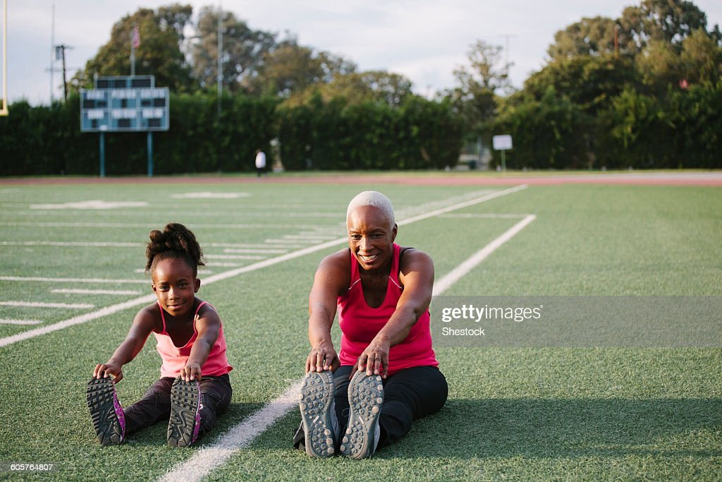 Grandmother and granddaughter stretching on football field : Stock Photo