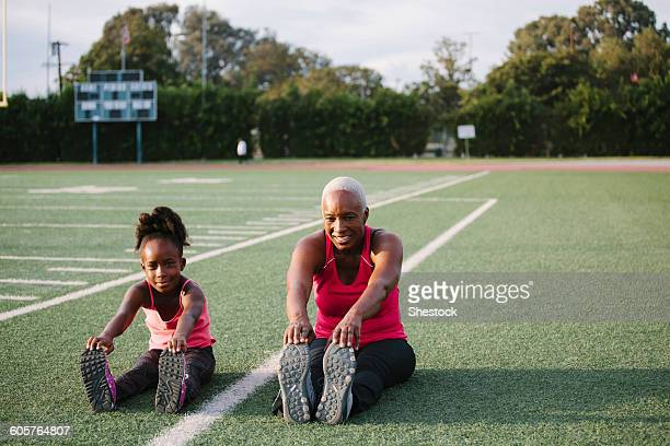 grandmother and granddaughter stretching on football field - daily sport girls stock pictures, royalty-free photos & images