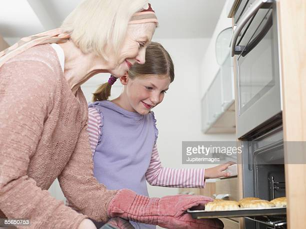 Grandmother and granddaughter taking scones from oven