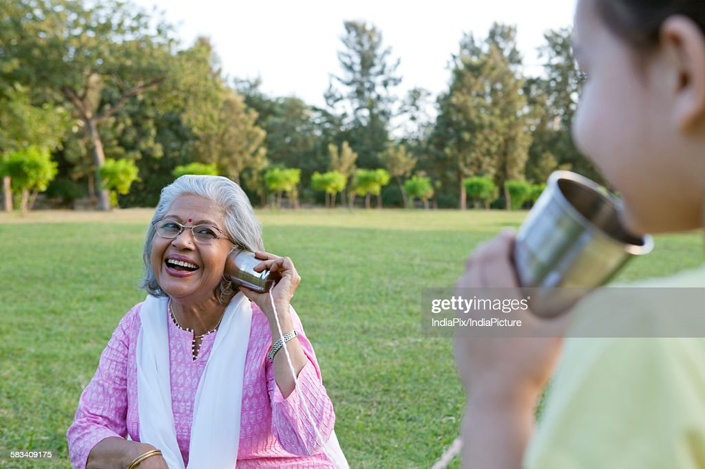 Grandmother and granddaughter talking through tin cans : Stock Photo