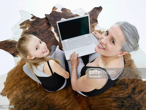 Grandmother and granddaughter (10-11) using laptop, portrait, elevated view