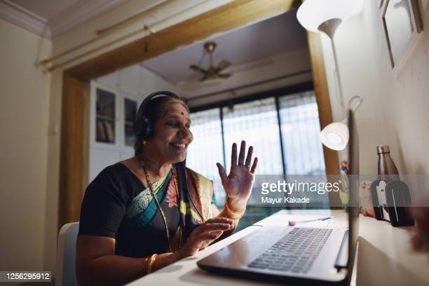 grandmother and granddaughter video conferencing using laptop - india stock pictures, royalty-free photos & images